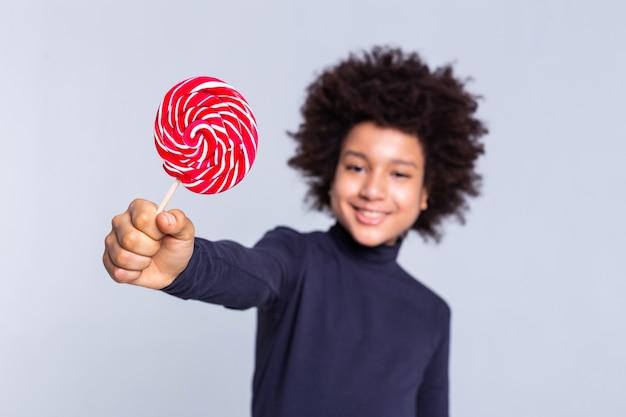 Wildes haar. entschlossener dunkelhaariger fröhlicher junge, der eine hand mit süßigkeiten darin herauszieht und extrem stolz aussieht looking