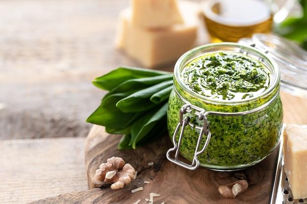 Wildes lauchpesto mit olivenöl und parmesankäse in einem glas auf einem holztisch. nützliche eigenschaften von ramson. blätter von frischem bärlauch. speicherplatz kopieren
