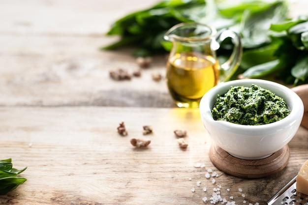Wildes lauchpesto mit olivenöl und parmesankäse in einem weißen keramikmörser auf einem holztisch. nützliche eigenschaften von ramson. speicherplatz kopieren.