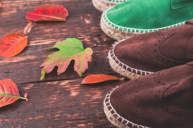 Wildlederstiefel espadrilles des browns und des grünen mannes auf hölzernem mit blättern.