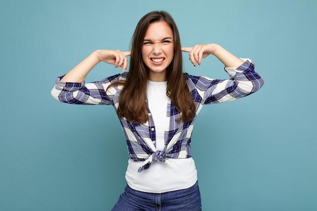 Will es nicht hören. junge emotionale positive attraktive brünette weibliche person lokalisiert auf blau