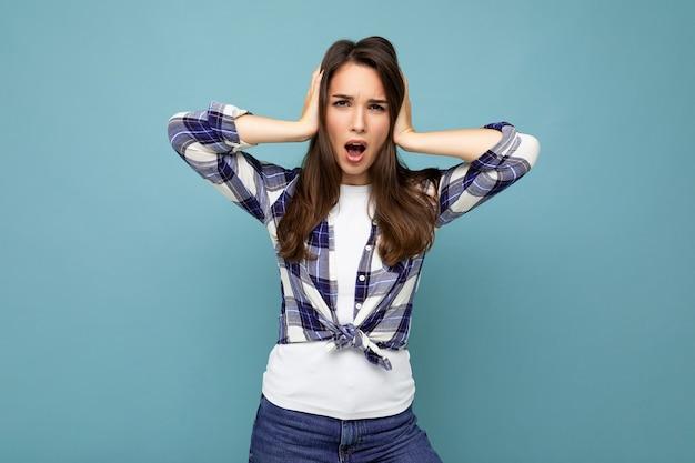Will es nicht hören! junge emotionale schöne brünette frau mit kariertem hemd isoliert auf blauem hintergrund mit kopierraum und ohrenbedeckung und schreien