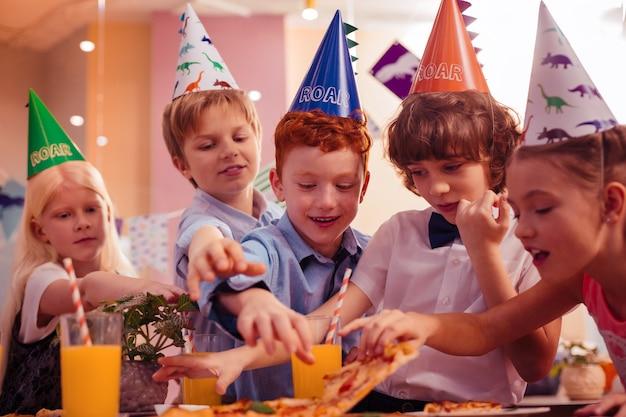 Will essen. begeisterte kinder, die beim abendessen ihre positive einstellung zum ausdruck bringen