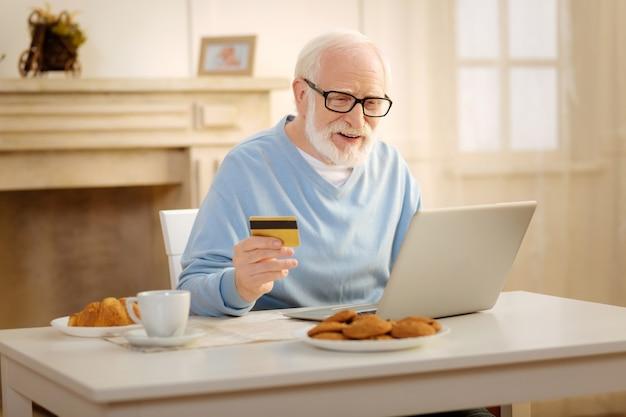 Will kaufen. hübscher reifer mann, der lächelt und kreditkarte hält, während alle bestellungen bezahlen
