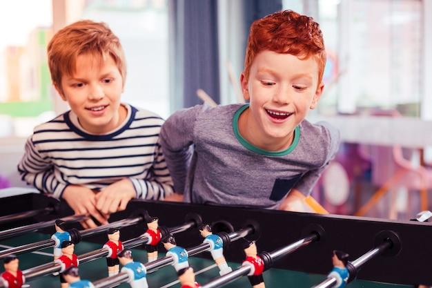 Will sehen. zwei kinder, die glasieren, sind bereit für das spiel und platzieren ihre künstlichen spieler