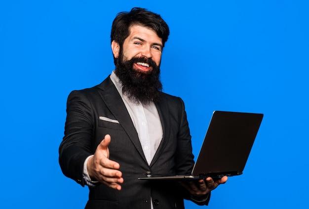 Willkommen geschäft. händedruck. geschäftsmann mit händeschütteln. geschäftsleute beim treffen. lächelnder bärtiger mann mit laptop.