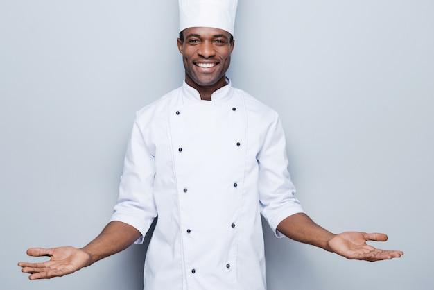 Willkommen in der welt des geschmacks. selbstbewusster junger afrikanischer koch in weißer uniform