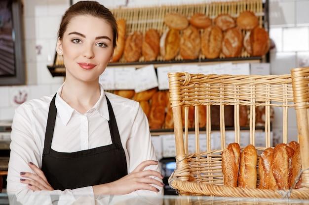 Willkommen in meinem laden! schuss einer schönen bäckerin, die im bäckereigeschäft aufwirft