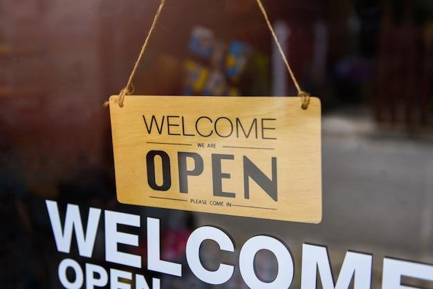 Willkommen offenes schild an der glastür des cafés
