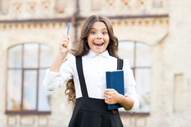 Willkommen zurück in der schule. schulmädchen formale uniform halten buch. dem wissen entgegen. studentenleben. schüler. intelligentes kind. intellektuelle aufgabe. kognitiver prozess. neues schulprojekt starten.