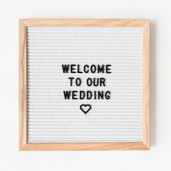 Willkommener text für die heirat auf holzrahmen gegen weißen hintergrund