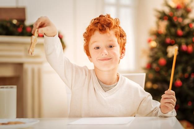 Willst du etwas. begeistertes ingwer-kind mit seinen augen voller glück, während es zu hause entspannt und lebkuchenplätzchen isst.