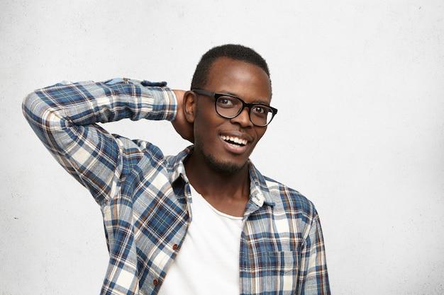 Willst du mich verarschen? glücklicher fassungsloser junger afroamerikanischer hipster, der brille und kariertes hemd trägt, das in aufregung schaut, erstaunt über gute unerwartete nachrichten, hand hinter seinem kopf hält