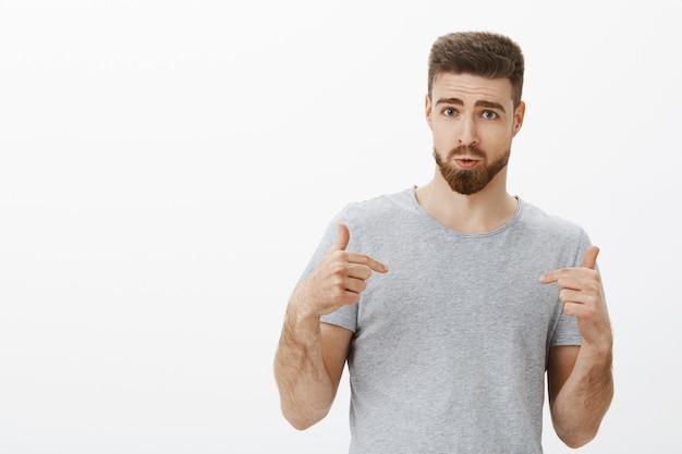 Willst du so einen perfekten körper haben? selbstbewusster gutaussehender mann mit stilvollem bart und frisur, die auf sich selbst zeigen, befragt und entschlossen, sich sicher zu fühlen, ernährungsprogramm für fitnessstudio-besucher zu empfehlen
