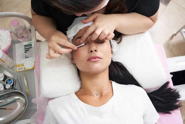 Wimpernlaminieren und bemalen von nahaufnahmen für schönheitsbehandlungen in der kosmetikklinik