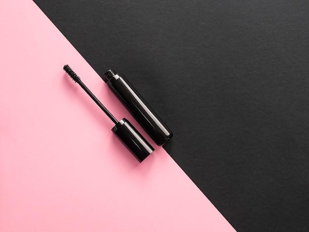 Wimperntusche auf rosa und schwarzem hintergrund.