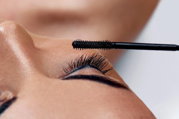 Wimperntusche. nahaufnahme des schönen jungen frauengesichtes mit schönheits-make-up, frischer weicher haut und langen schwarzen dicken wimpern, die wimperntusche mit kosmetischem pinsel anwenden. bilden