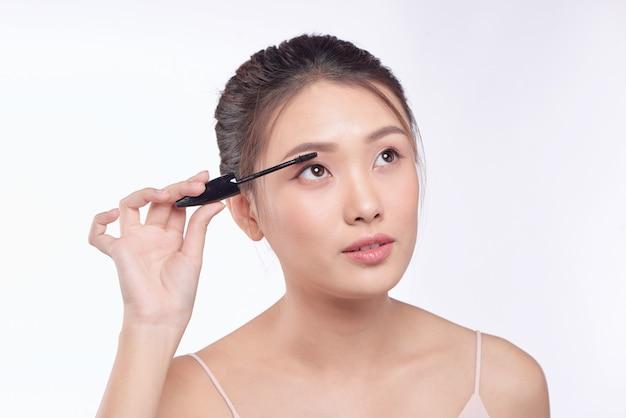 Wimperntuschefrau, die augen schminkt. asiatische weibliche modellgesichtsnahaufnahme mit augenbürste auf wimpern.