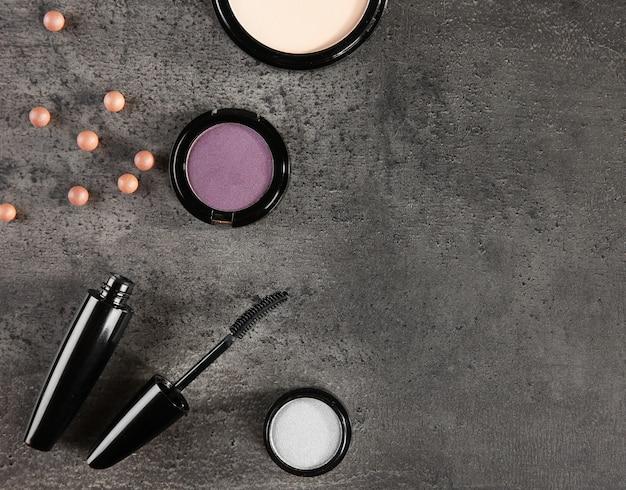 Wimperntuschenpinsel und kosmetik auf grauem hintergrund, kopienraum