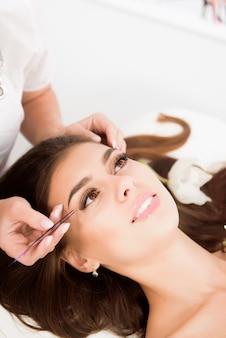 Wimpernverlängerung durch professionelle lashmaker im schönen salon. frau, die während der wimpernvergrößerung auf kosmetologischem trainer liegt.