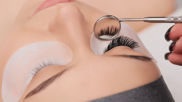 Wimpernverlängerungsverfahren aus der nähe. falsche wimpern. make-up und beauty-konzept.