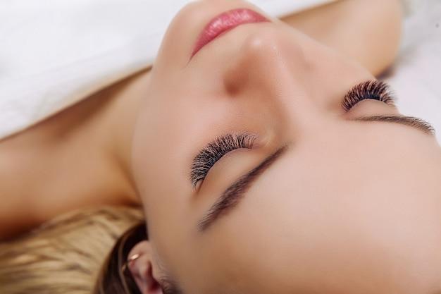 Wimpernverlängerungsverfahren frau auge mit langen blauen wimpern nahaufnahme selektiven fokus