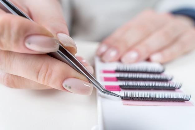 Wimpernverlängerungsverfahren nahaufnahme eines meisters bei der arbeit künstliches wimpernverlängerungsmaterial