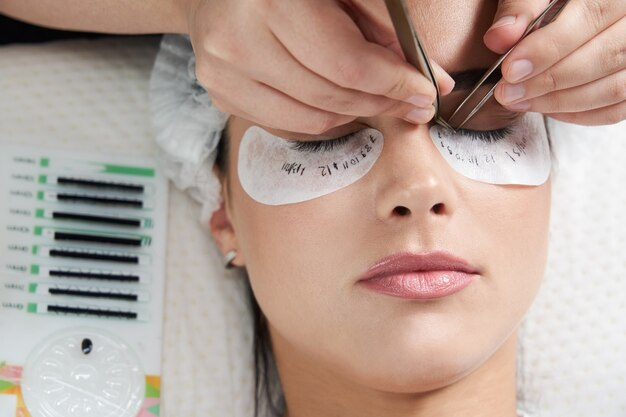 Wimpernverlängerungsverfahren nahaufnahme schöne frau mit langen wimpern in einem schönheitssalon