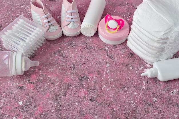 Windeln und babyzubehör auf einer rosa hintergrundoberansicht mit kopienraum.