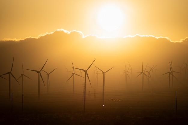 Windenergieanlage mit windmühlen und orangefarbenem himmelssonnenuntergang