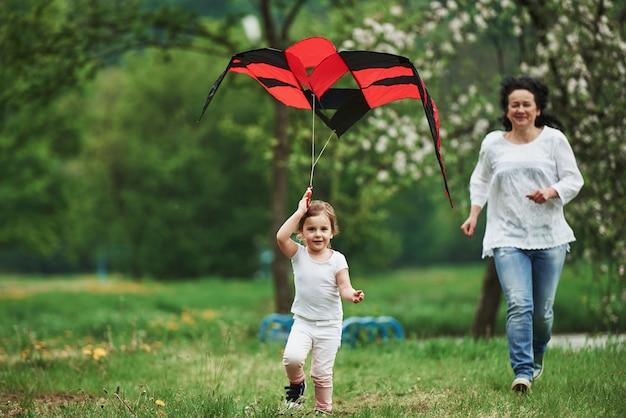 Windiger tag, perfekt. positives weibliches kind und großmutter, die mit rotem und schwarzem drachen in den händen draußen laufen