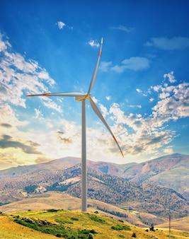 Windkraftanlage auf einem hügel gegen den sonnenuntergangshimmel