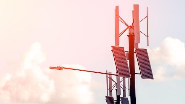 Windkraftanlage mit sonnenkollektoren auf säule. allgemeines stadtlicht mit dem sonnenkollektor angetrieben auf blauem himmel mit wolken