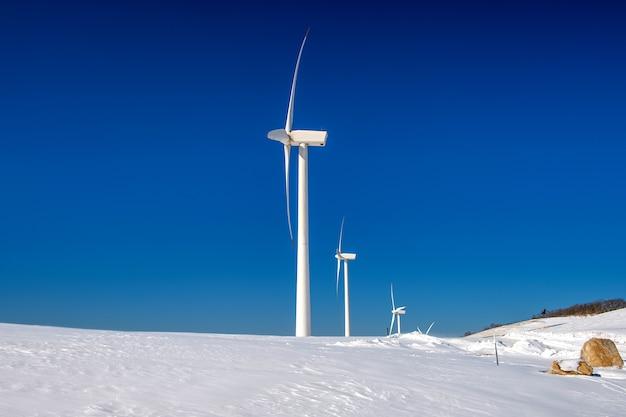 Windkraftanlage und blauer himmel in der winterlandschaft