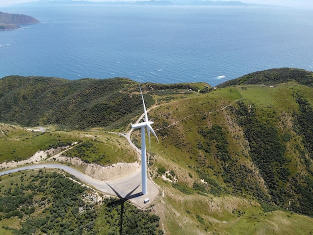 Windkraftanlage zur stromerzeugung auf einem grünen windpark mit wunderschönem meerblick