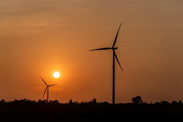 Windkraftanlagebauernhof und landwirtschaftliche felder mit lichtstrahlen bei sonnenuntergang