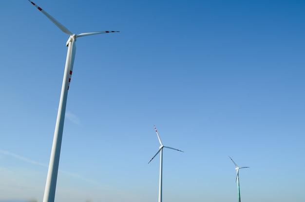 Windkraftanlagen in einem grünen feld und blauem himmel.