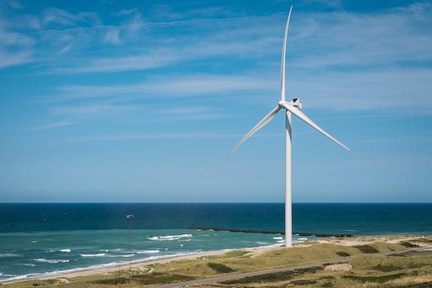 Windmühle am strand in der nähe des schönen meeres unter dem bewölkten himmel