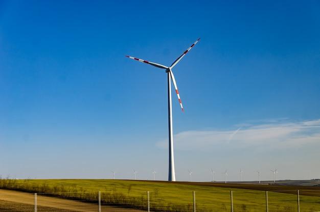Windmühle in einem grünen feld gegen einen blauen himmel. natürlich freundliche rohstoffgewinnungssysteme.
