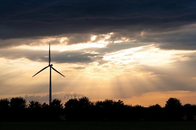 Windmühle mit bewölktem abendhimmel im hintergrund