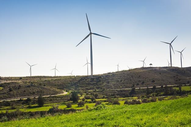 Windmühlen während des hellen sommertages. grüne wiese mit windkraftanlagen zur stromerzeugung.