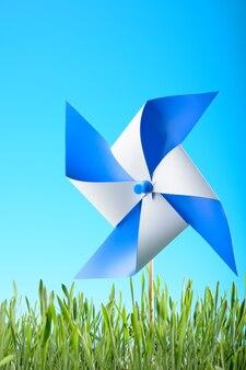 Windmühlenspielzeug auf grünem gras gegen den himmel