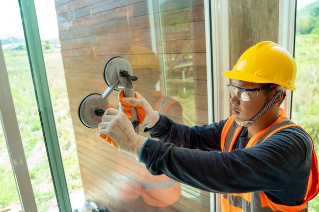 Windows-installationsarbeiter, männlicher industriearbeiter bei der fensterinstallation auf der baustelle.