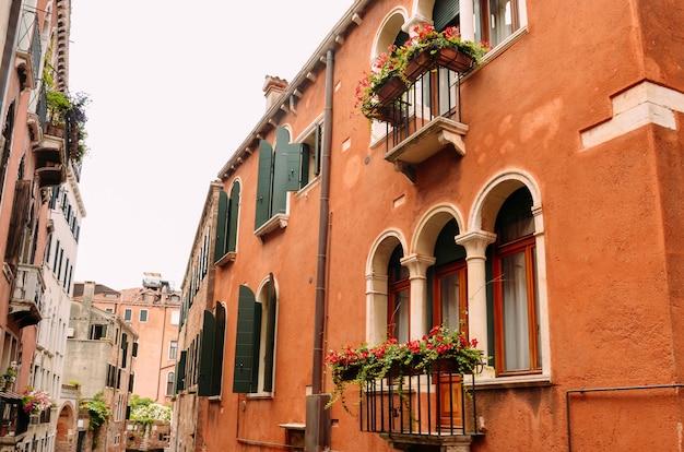 Windows und balkone mit blumen in venedig, italien.