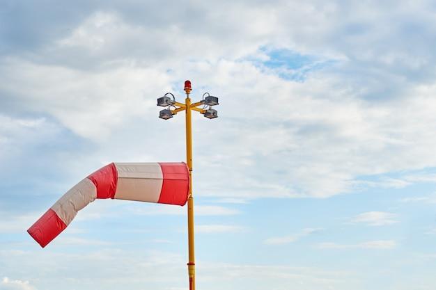Windsack. indikator für wehenden wind gegen bewölkten himmel