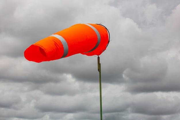 Windsackanzeige des windes auf dem chemischen konus des tanks, der windrichtung und -stärke anzeigt. horizontal fliegender windsack (windfahne) mit wolkenhimmel im hintergrund.