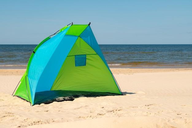 Windschutzzelt an einem sandstrand am meer.