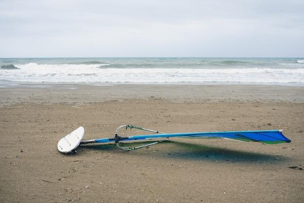 Windsurfbretter im sand eines spanischen strandes, während surfer auf die richtige welle warten.