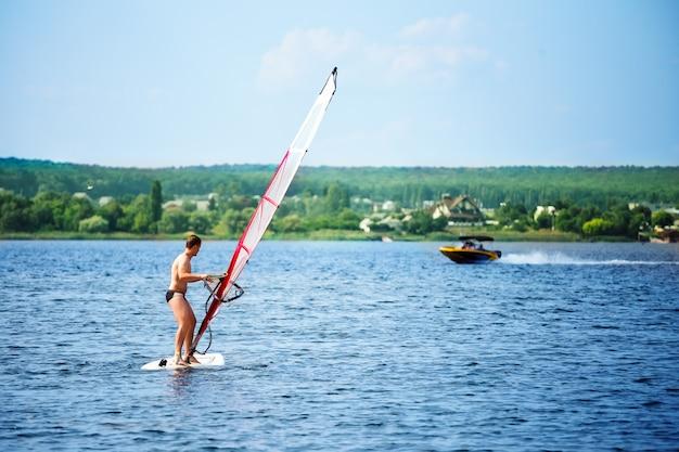 Windsurfer an bord mit einem weißen segel, das wegschwimmt