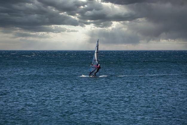 Windsurfer üben mit ihrem surfbrett an der adria